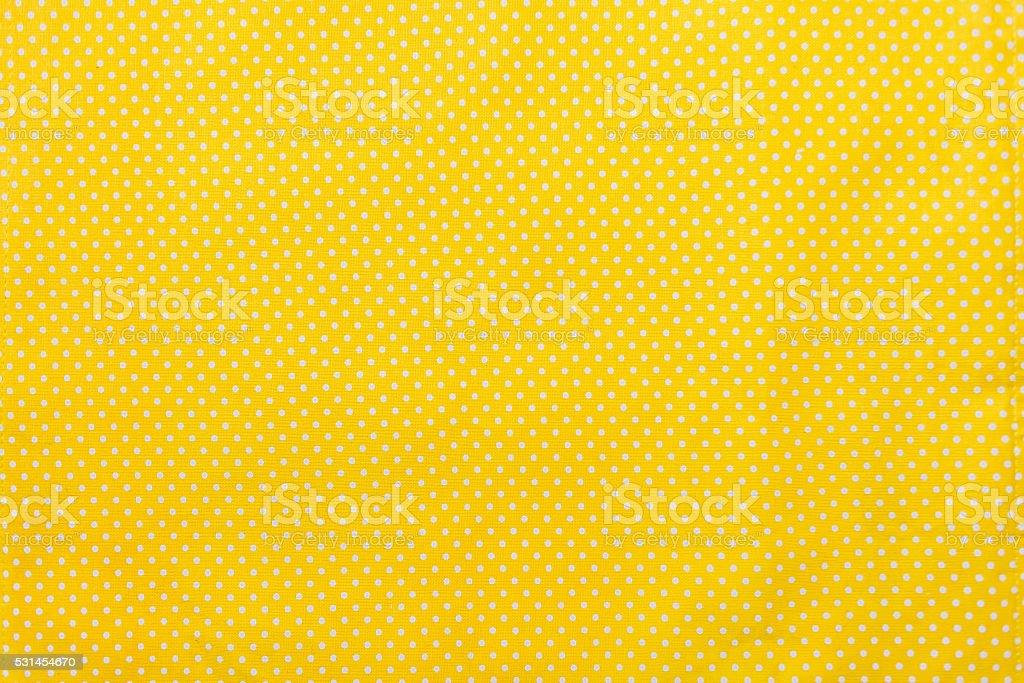 Yellow and white polka dots tablecloth picnic texture. stock photo