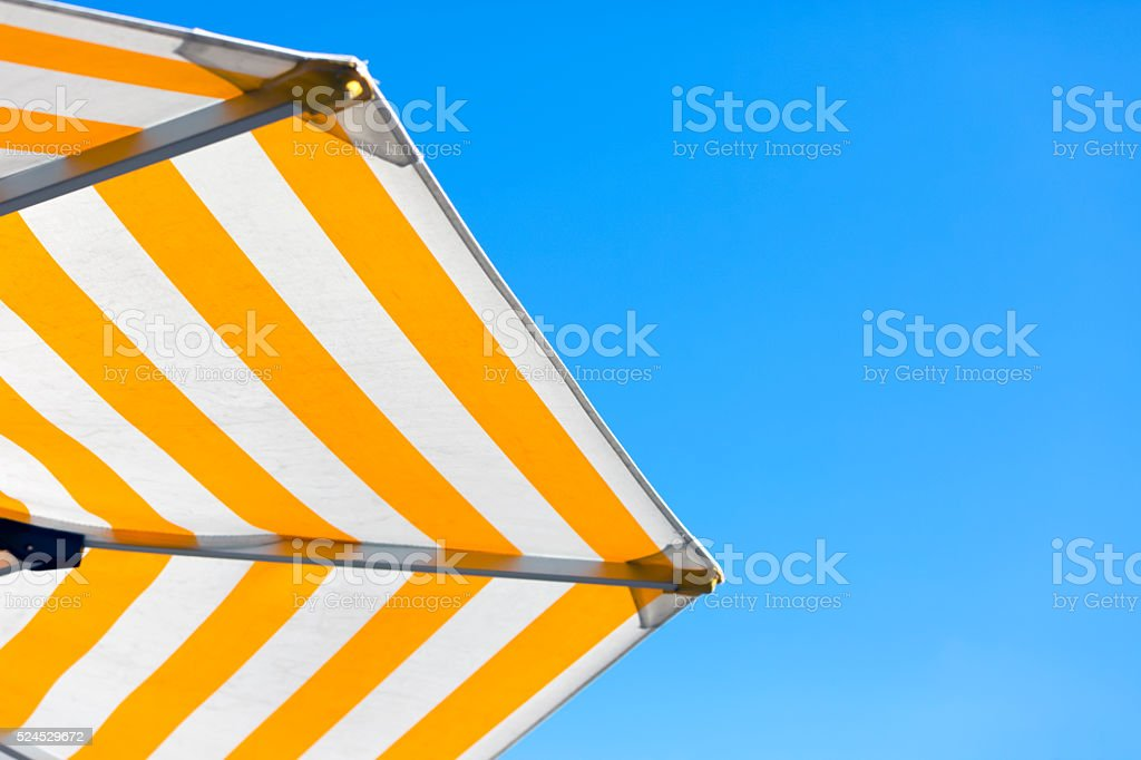 Yellow and white stired umbrella against blue sky, copy space stock photo