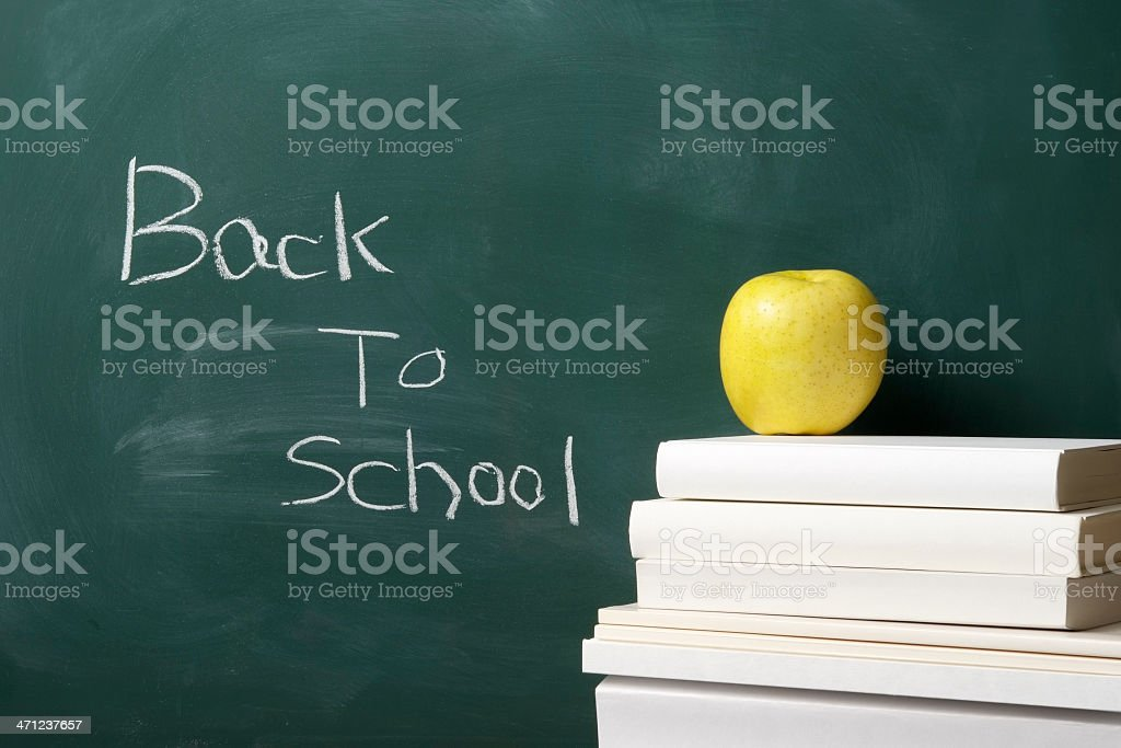 Yellow apple on stacked blank books against blackboard royalty-free stock photo