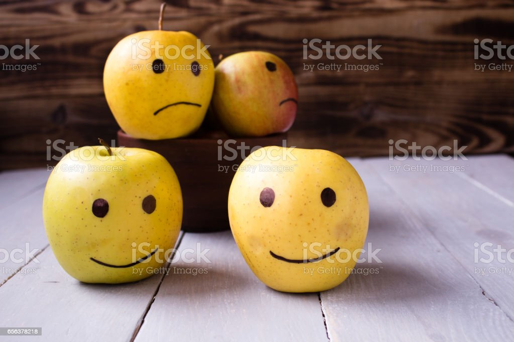 yellow apples with drawn emotions stock photo