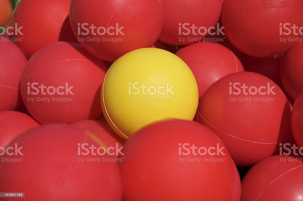 Yellow ball among red balls royalty-free stock photo