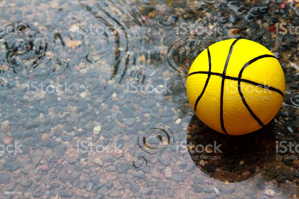 Yellow ball in wet field stock photo