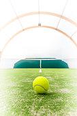 Yellow ball on the tennis court interior