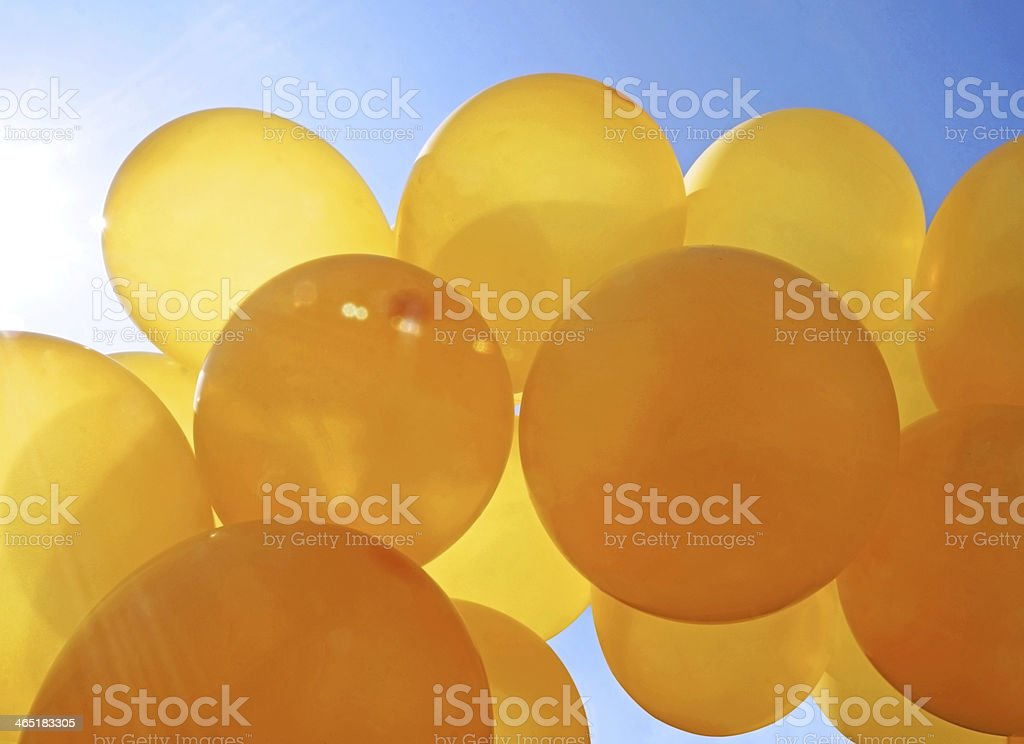 Yellow balloons against blue sky stock photo