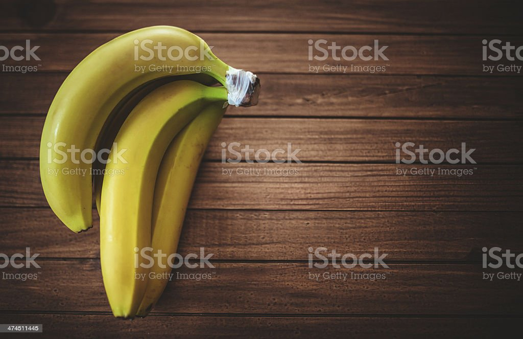 yellow banana on vintage wooden background stock photo