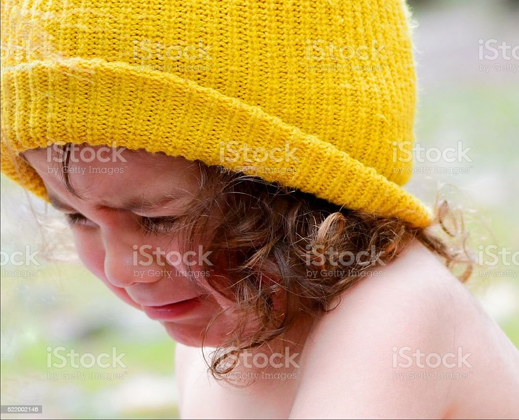 Yellow Beanie on Curley Haired Boy Crying stock photo