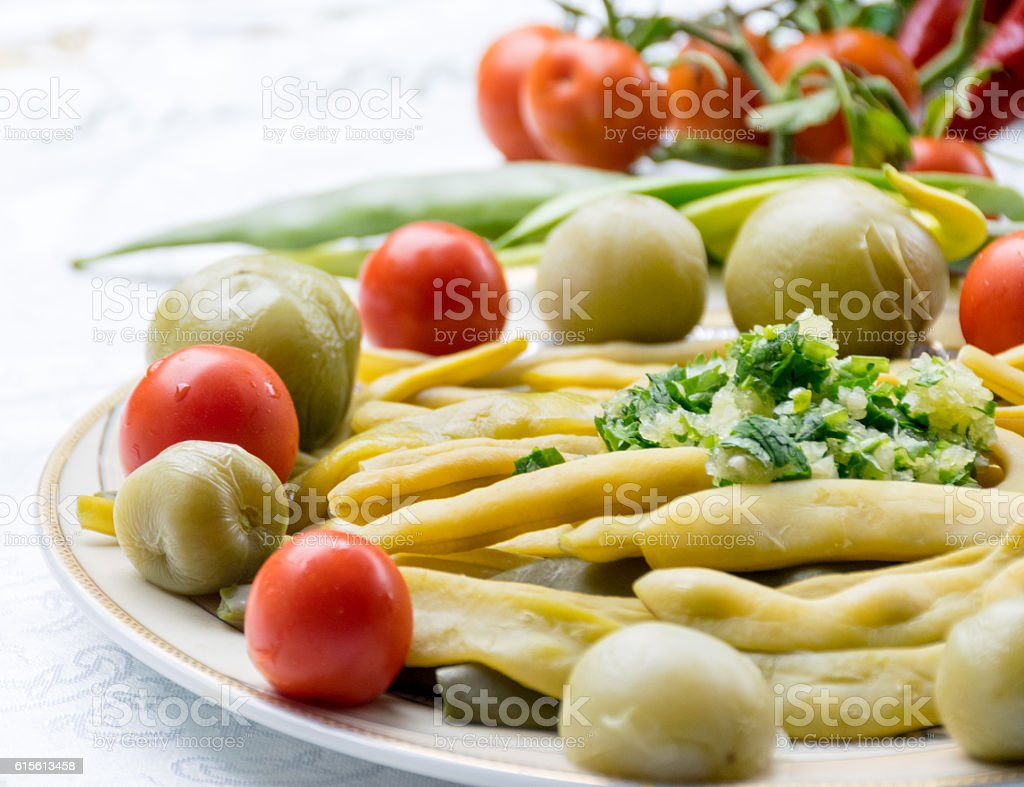 yellow beans, green and red tomatoes, garlic and herbs stock photo