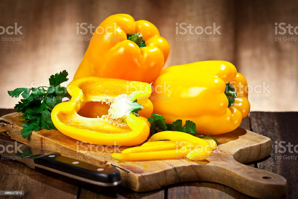 Yellow bell peppers on wooden cutting board stock photo