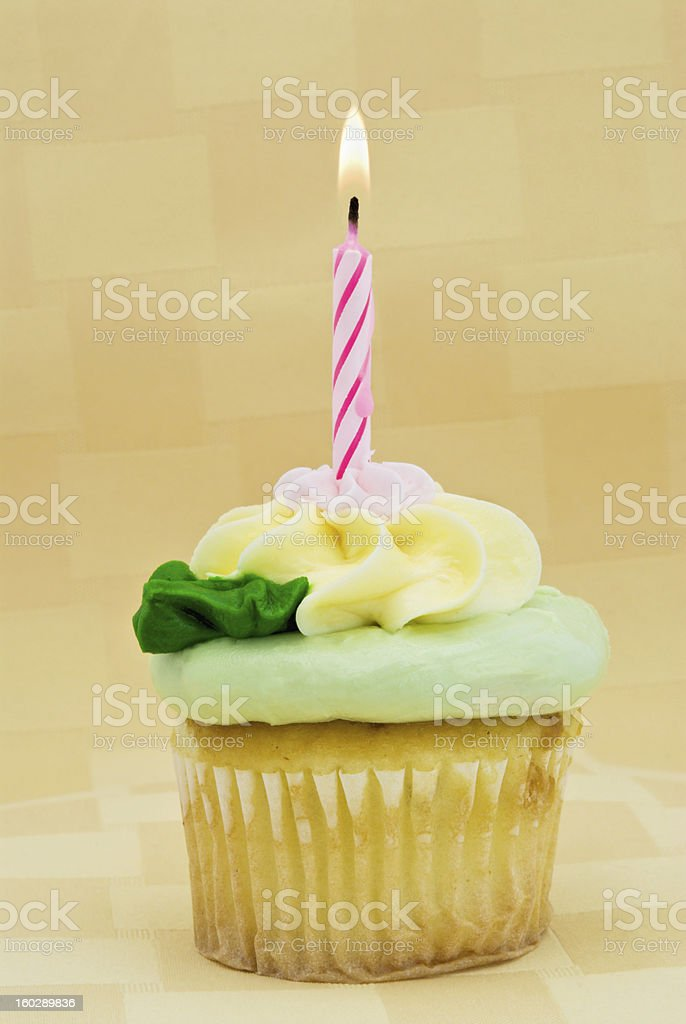 yellow birthday cupcake with pastel colored icing and one candle royalty-free stock photo