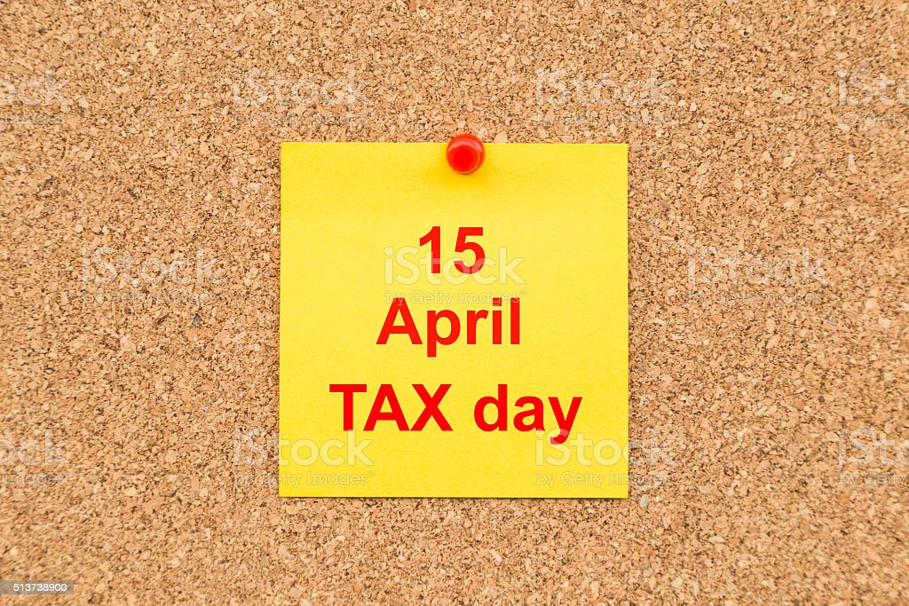 Yellow blank note and written 15 April TAX Day stock photo