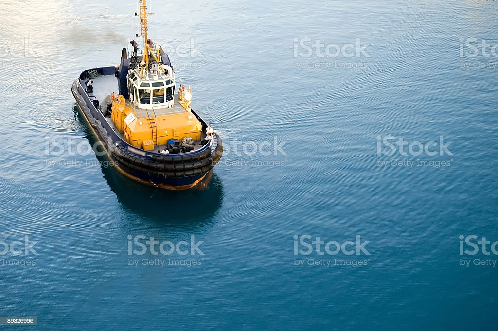 Yellow, blue and black harbor boat moving through the water royalty-free stock photo