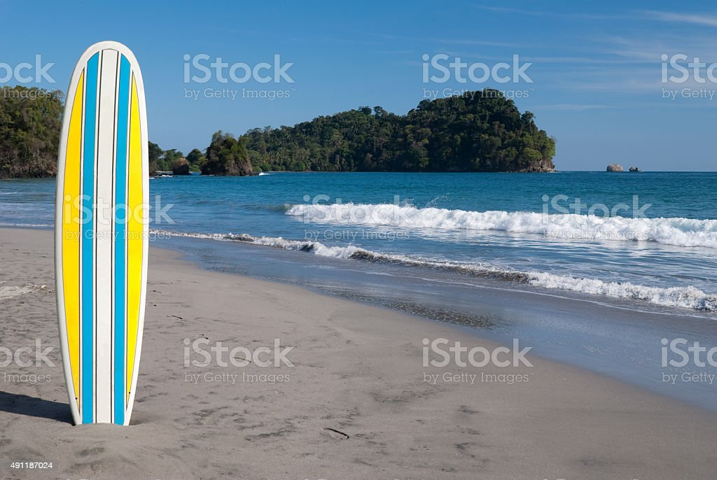 Yellow , blue and white surfboard on beach in Costa Rica stock photo