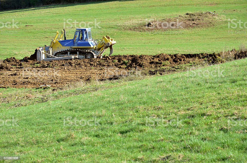 Yellow blue bulldozer working on field stock photo