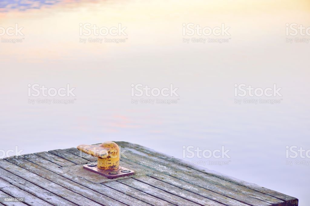 Yellow bollard, or a harbor post, on a wooden pier. stock photo