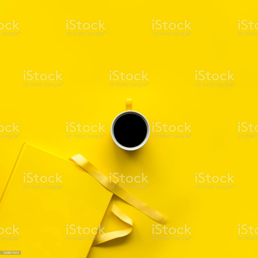 Yellow book and coffee on yellow background stock photo