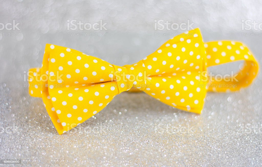 Yellow bow tie on silver background stock photo