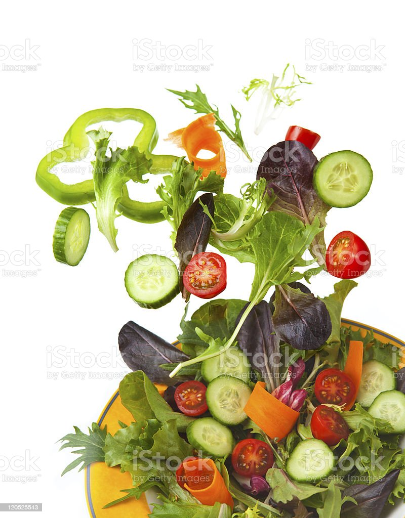 Yellow bowl containing mixed salad tossed in the air stock photo