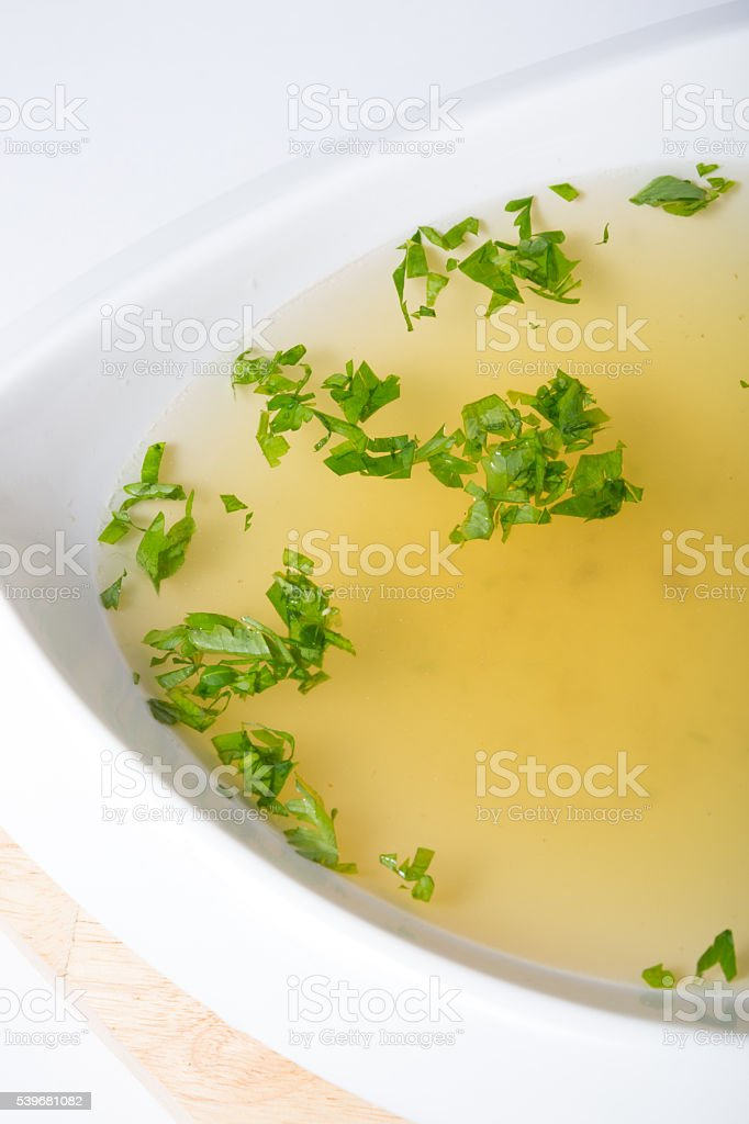 Yellow broth with herbs stock photo