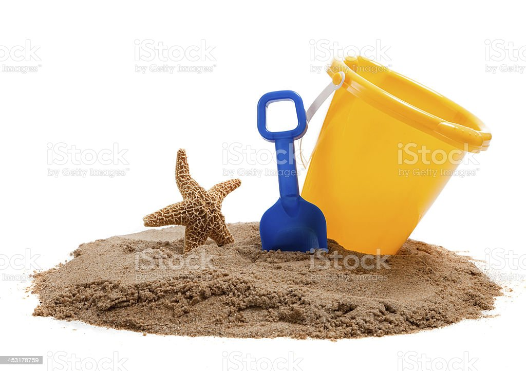 Yellow Bucket on a beach with blue shovel and starfish stock photo