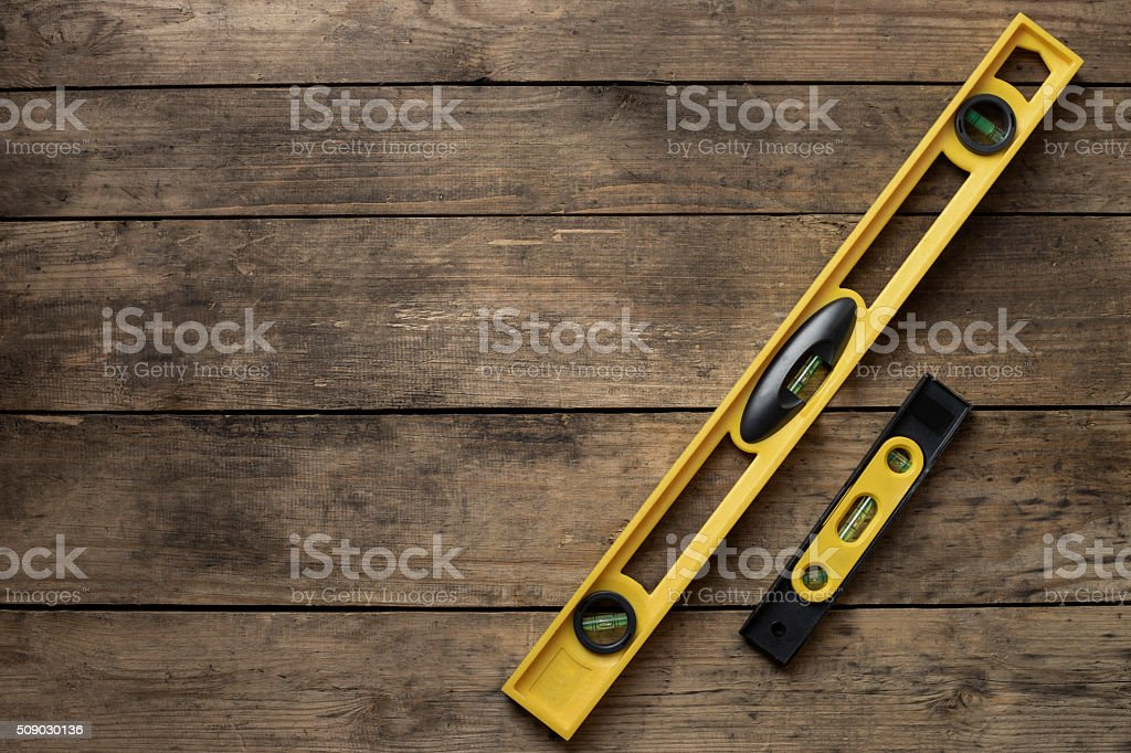 Yellow building level on old wood table stock photo