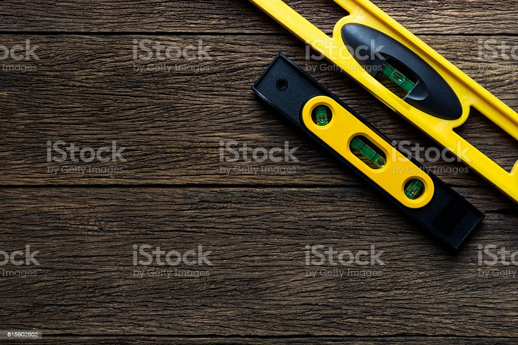 Yellow building levels on old wood table stock photo