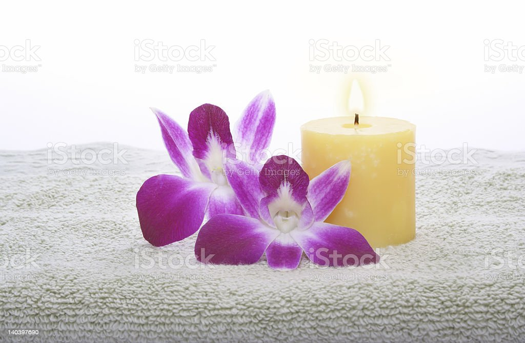 Yellow Candle and Orchid on Green Towel royalty-free stock photo