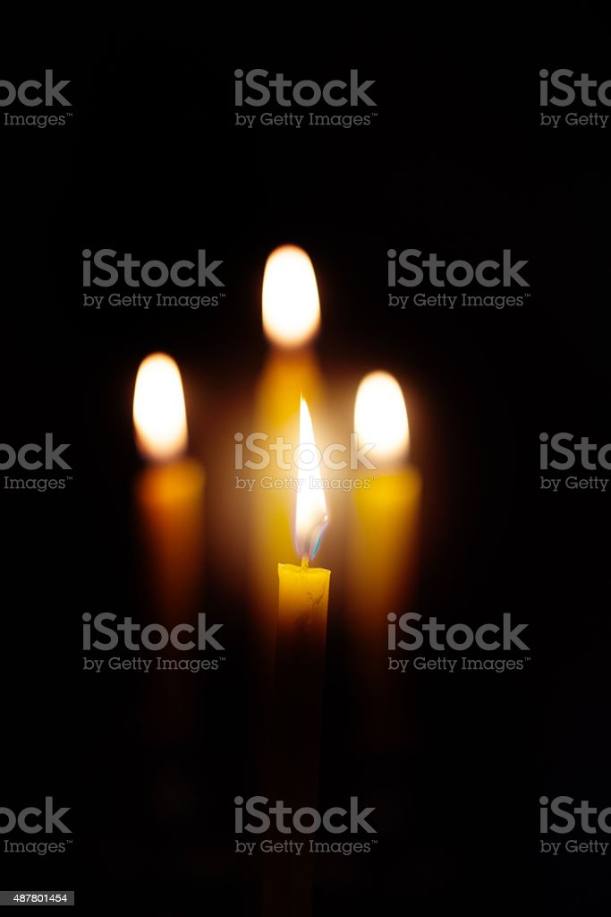 yellow candle lit on black background. stock photo