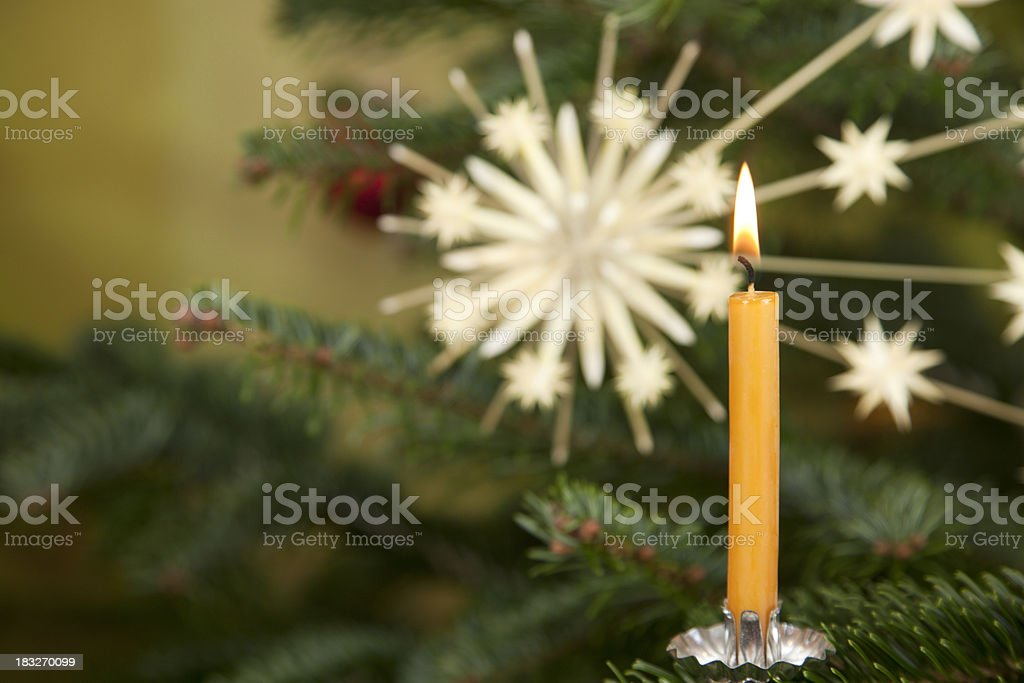Yellow candle on decorated christmas tree royalty-free stock photo