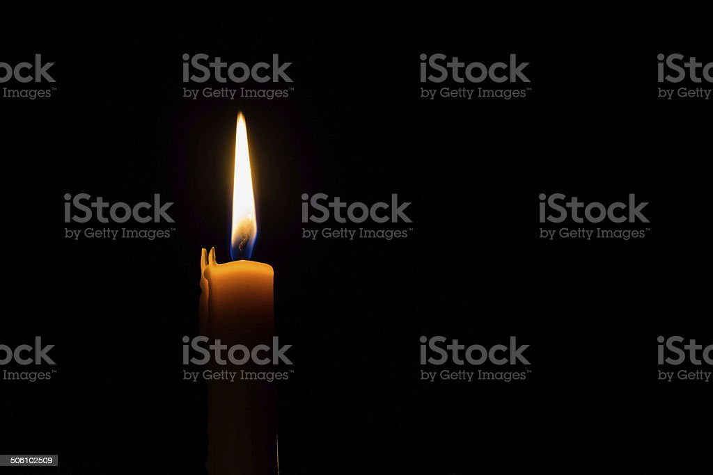 Yellow candle on the dark background stock photo