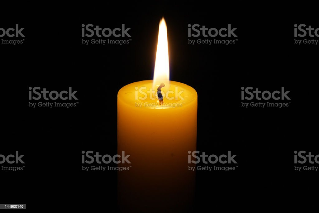 Yellow candle with fire on black background stock photo