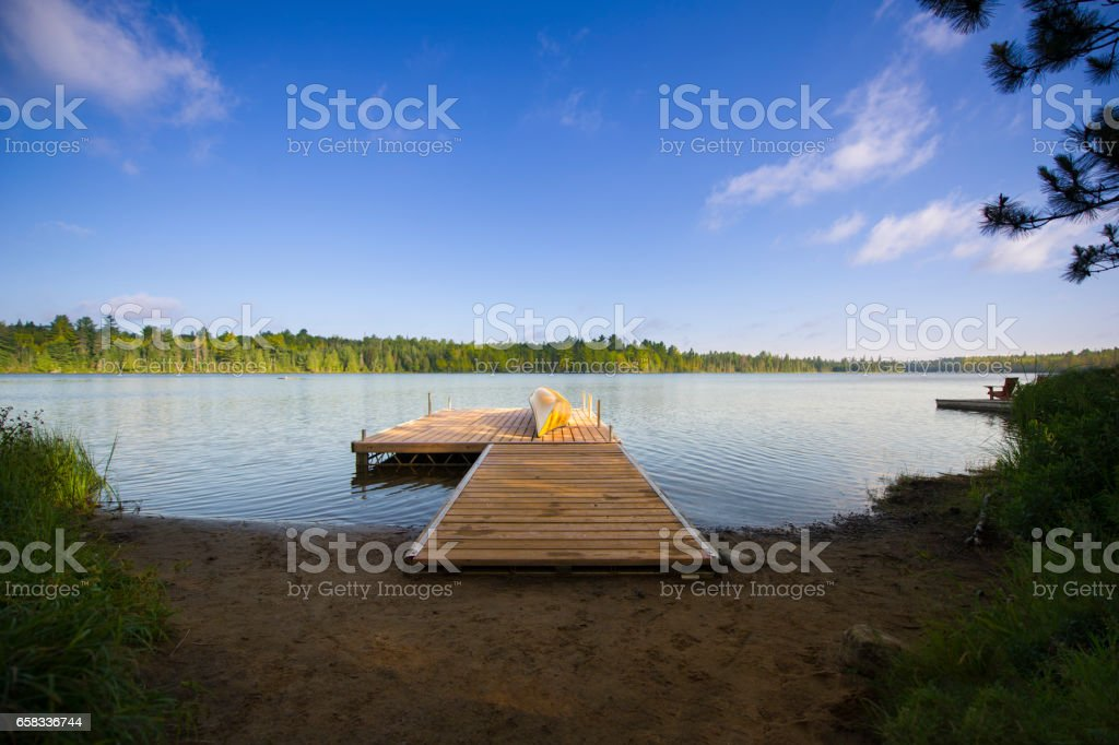 Yellow canoe on a lake deck stock photo