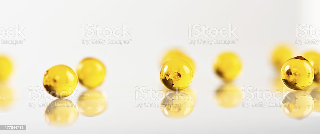 yellow capsules isolated on white royalty-free stock photo