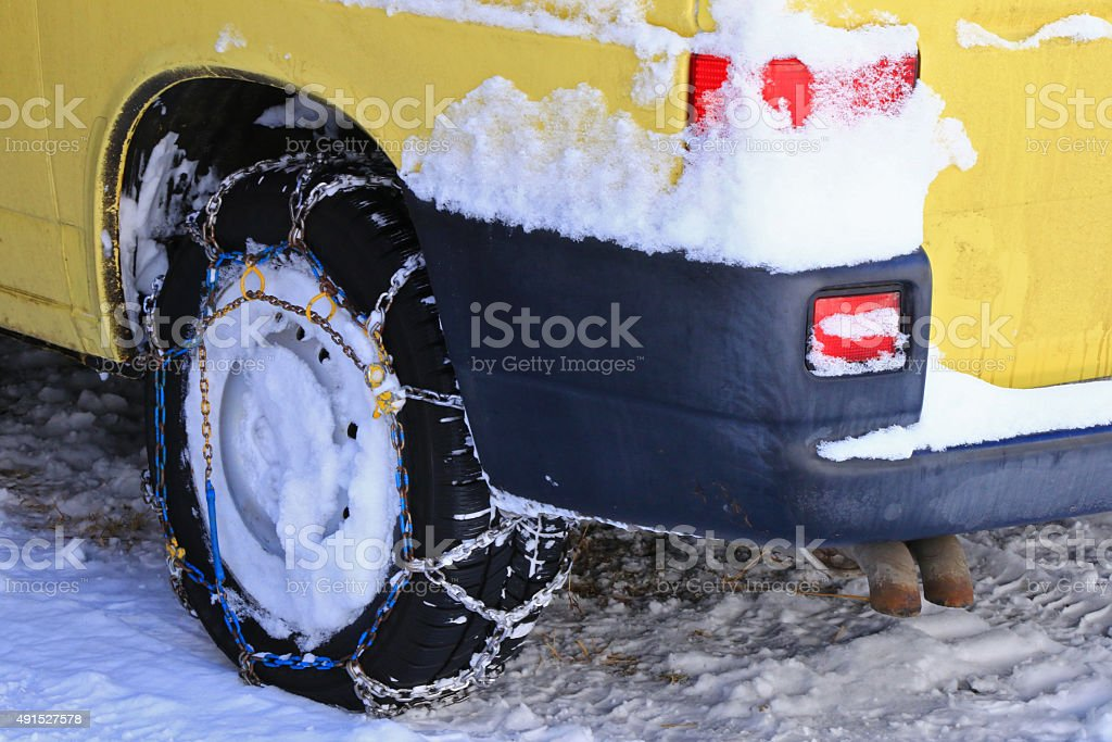 Yellow car with snow chains (tire chains) during winter stock photo