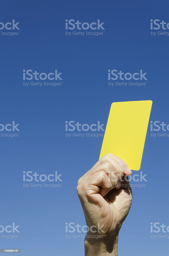 Yellow card in the hand against blue sky stock photo