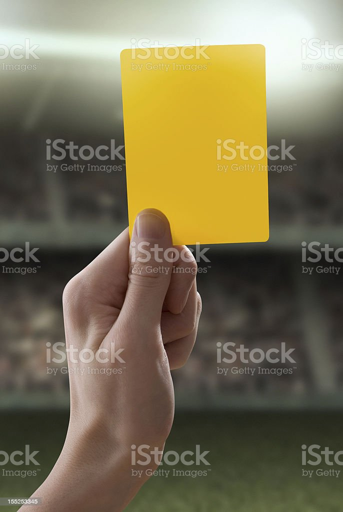 Yellow card with hand from referee giving a penalty stock photo
