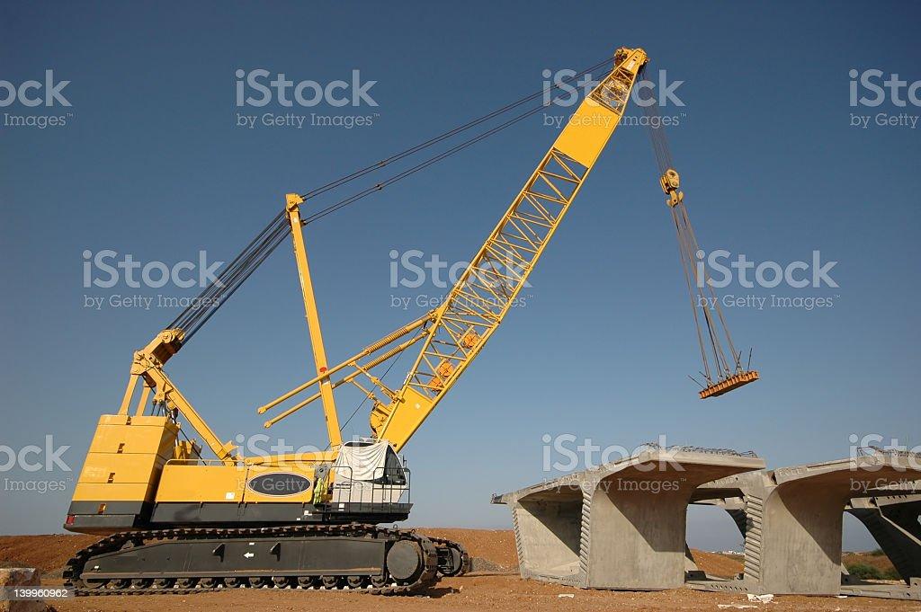 Yellow caterpillar crane constructing concrete roadway royalty-free stock photo