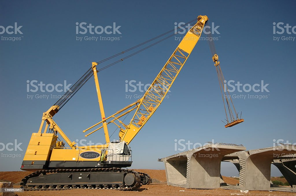Yellow caterpillar crane constructing concrete roadway stock photo