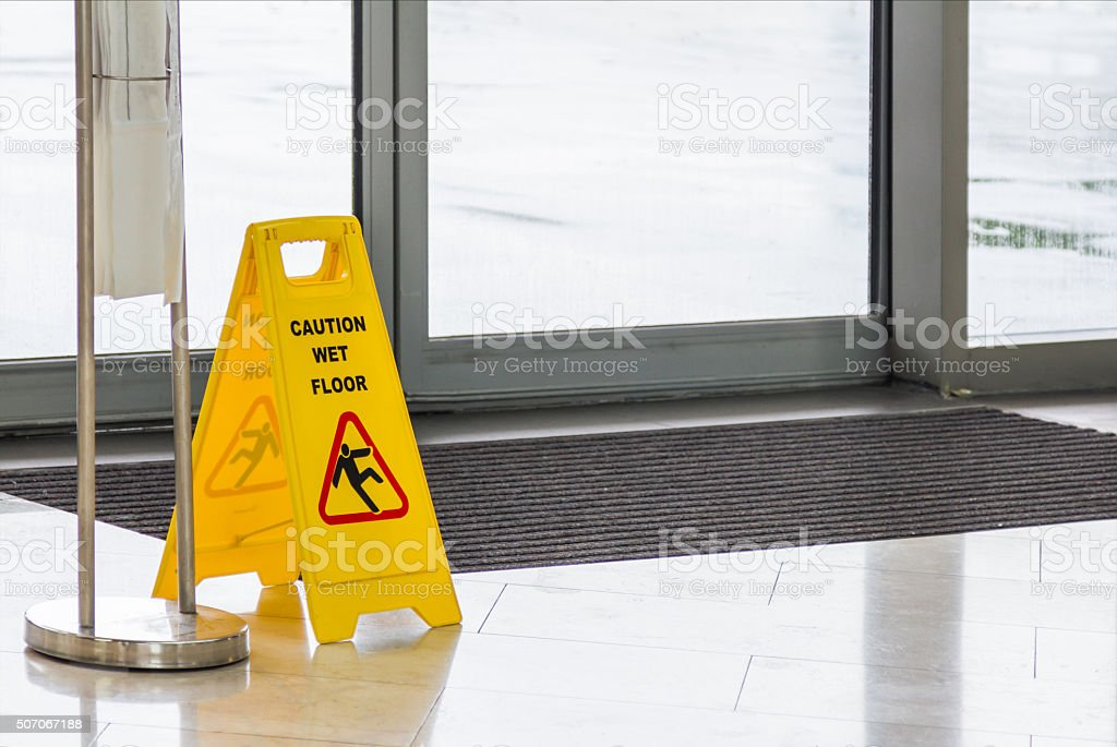 Yellow Caution slippery wet floor sign on background. stock photo