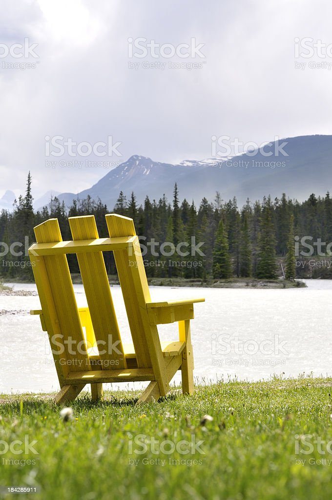 Yellow chair on bank of river portrait stock photo
