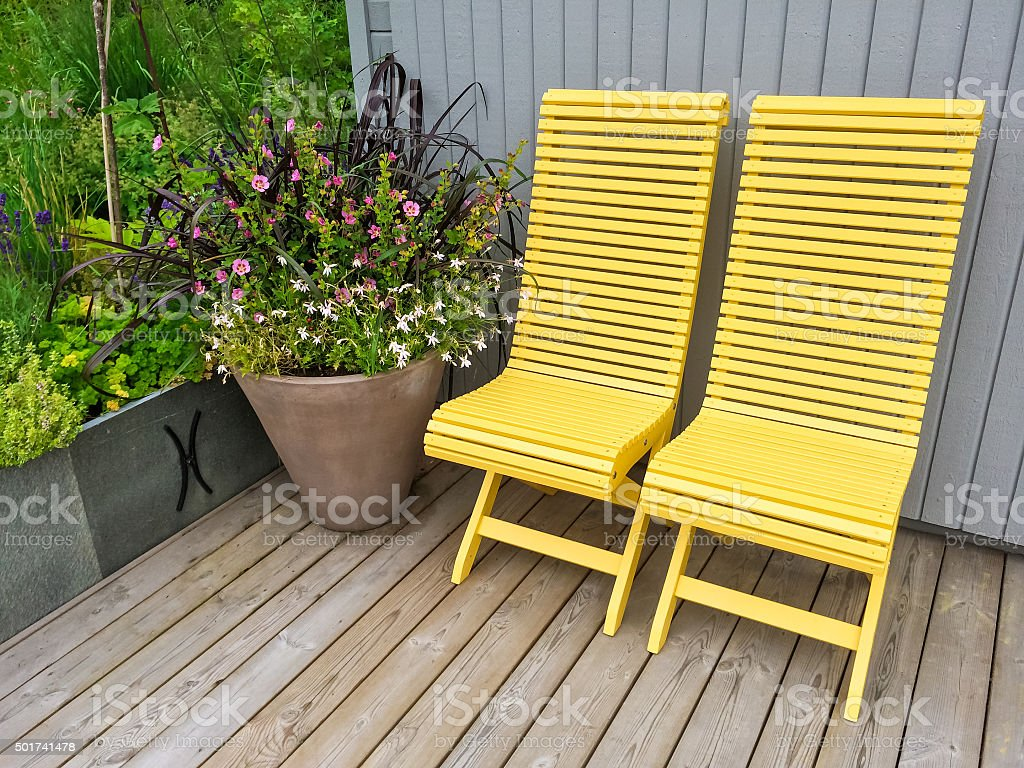Yellow chairs and flowers decorating house exterior stock photo