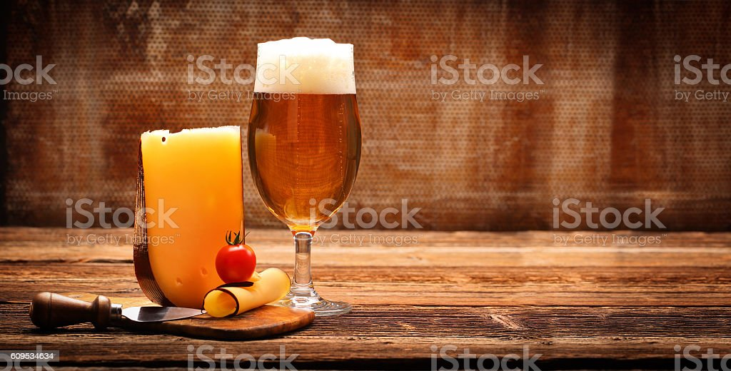Yellow cheese appetizer and beer stock photo
