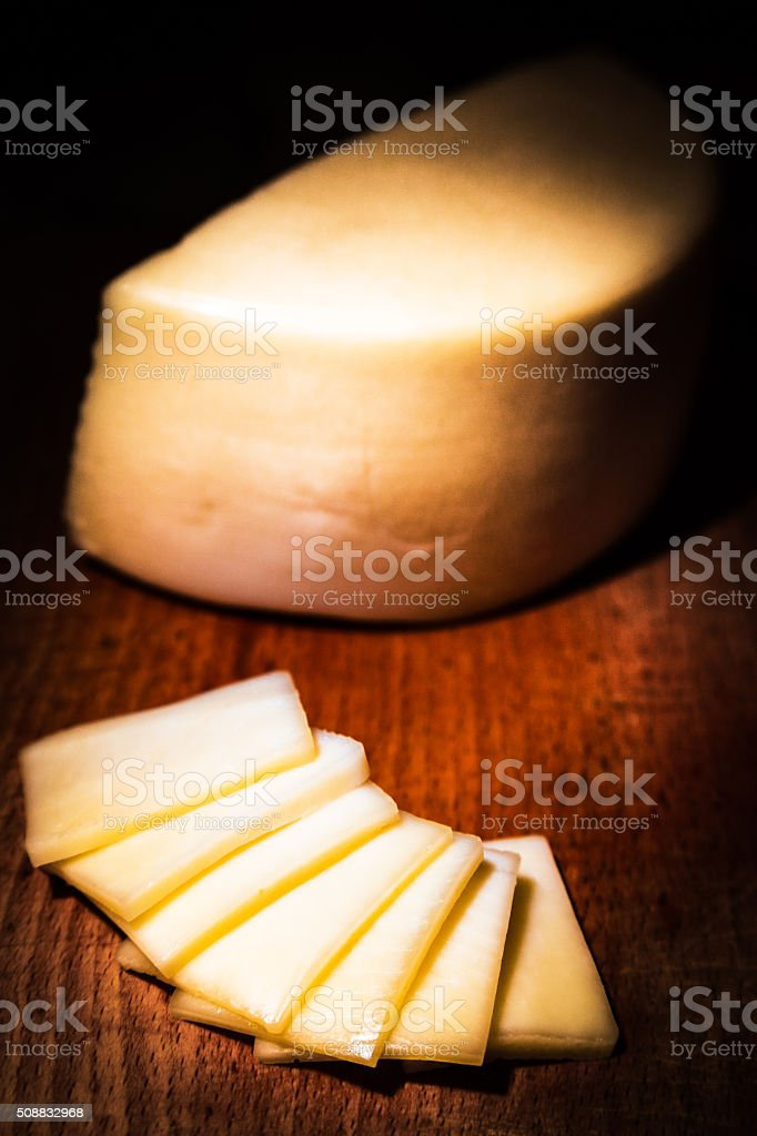 Yellow cheese, portion of Gouda on vintage wooden background stock photo