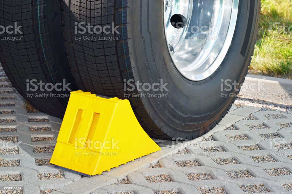 Yellow chock at the wheel of a parked truck stock photo