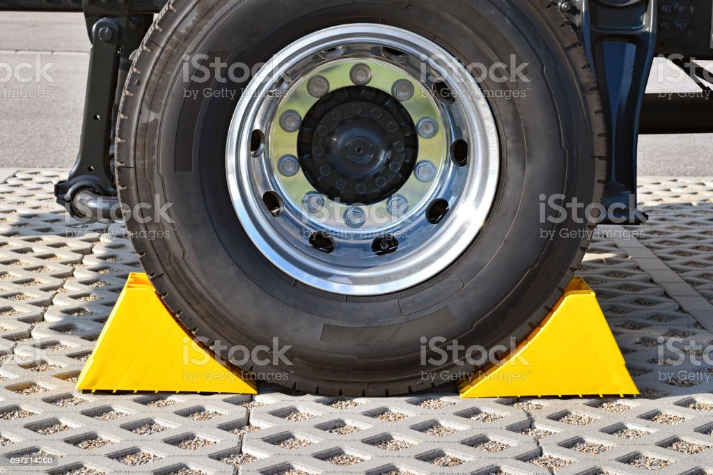 Yellow chocks at the wheel of a parked truck stock photo