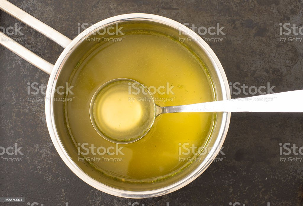 Yellow clear broth in a silver saucepan with ladle stock photo