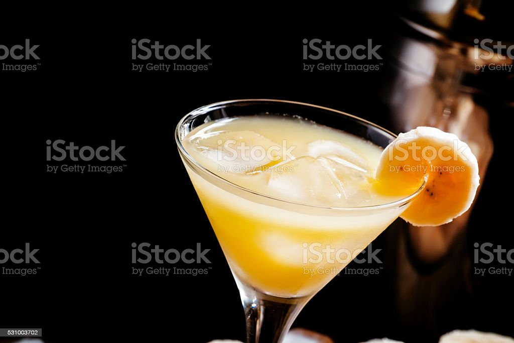 Yellow cocktail with whiskey, banana and ice stock photo