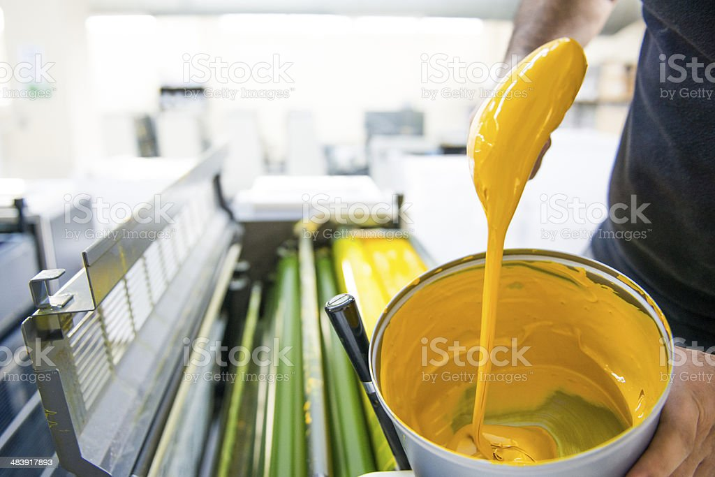 The workers put the yellow color printing machine