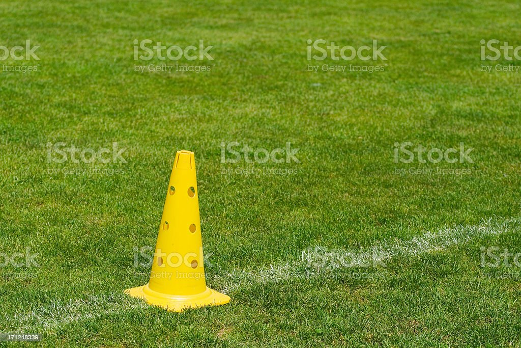 Yellow cone on a playing field royalty-free stock photo