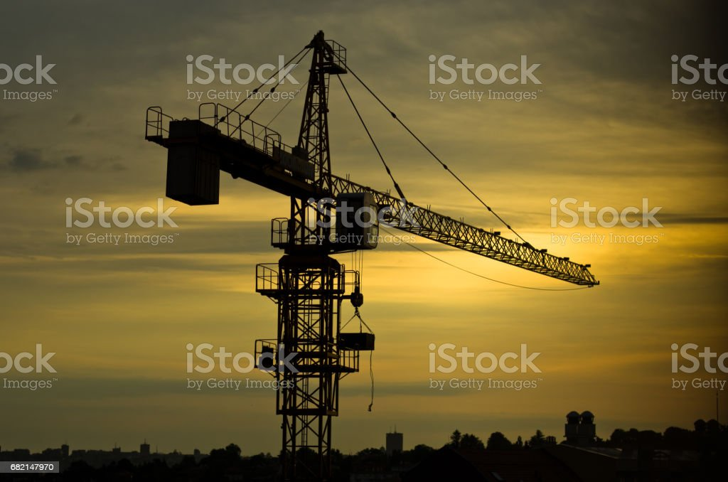 Yellow construction crane against cloudy sky at sunrise in Belgrade stock photo