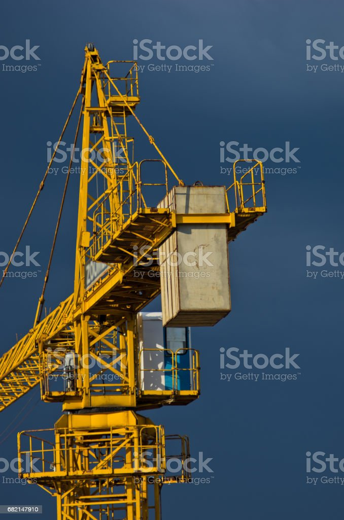 Yellow construction crane against dark blue sky in Belgrade stock photo